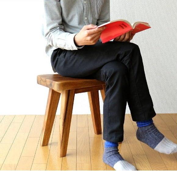モンキーポッドの木製スツールに座る男性