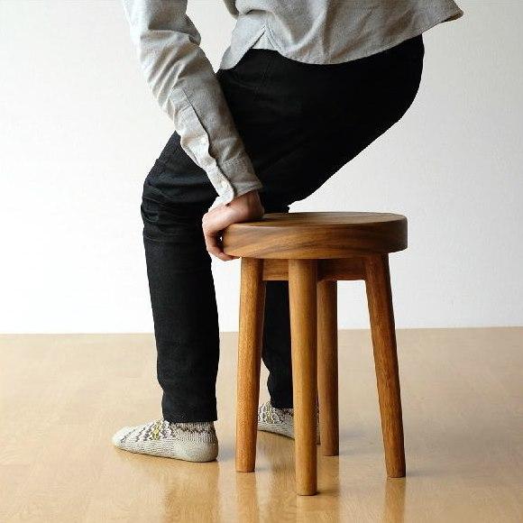 可愛い木の丸スツールに座る男性