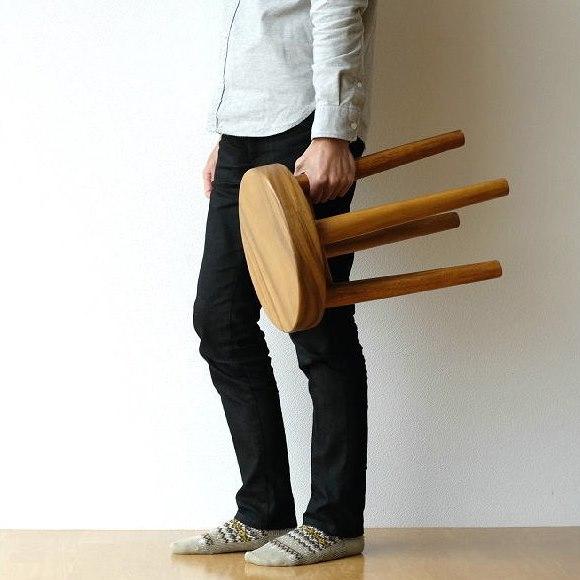 モンキーポッド無垢材の丸いスツールを持ち歩く男性
