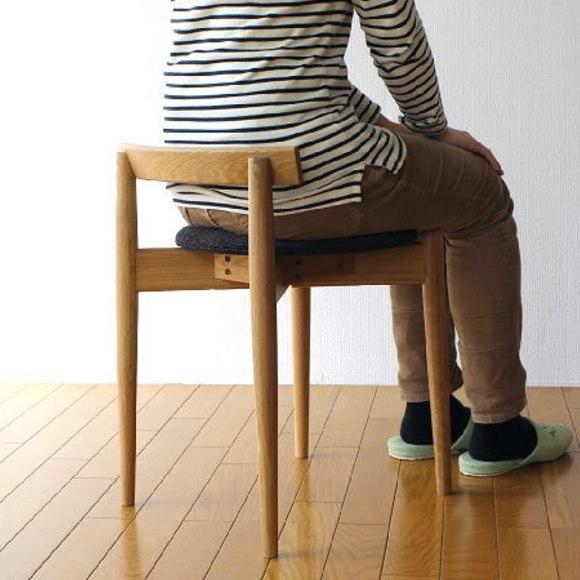低い背もたれの北欧スツールに座る男性