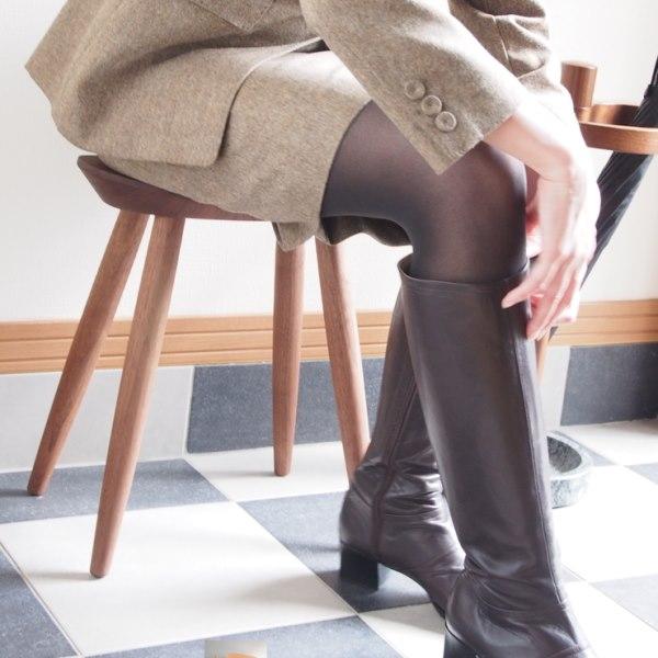 玄関椅子に座ってブーツを履く女性