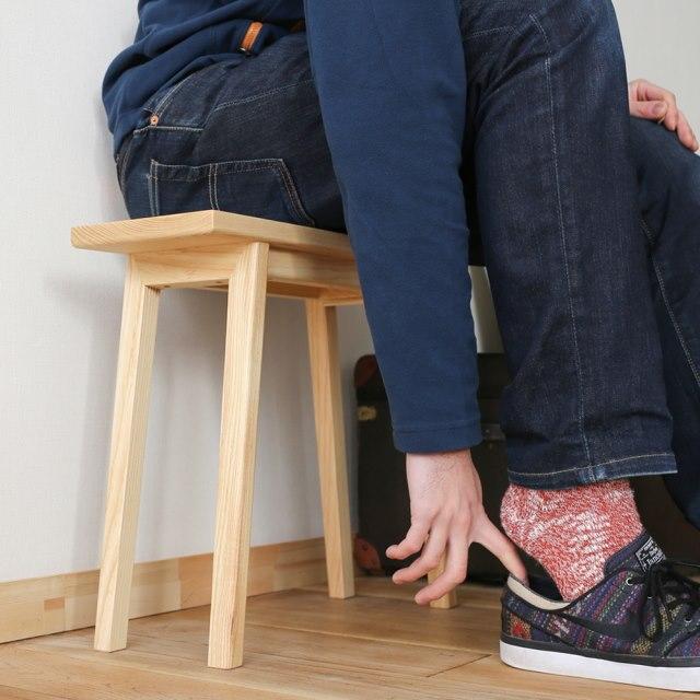 匠工芸のスリムなプレーン・スツールに座って玄関で靴を履く女性