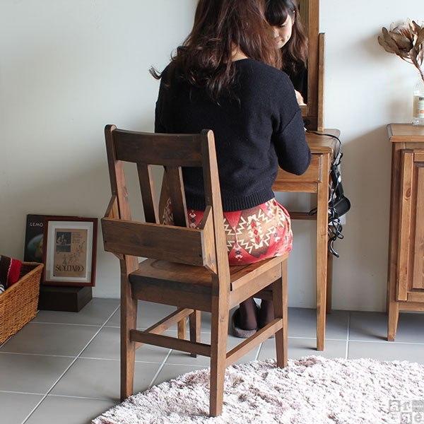 鏡台の前のチャーチチェアに座る女性