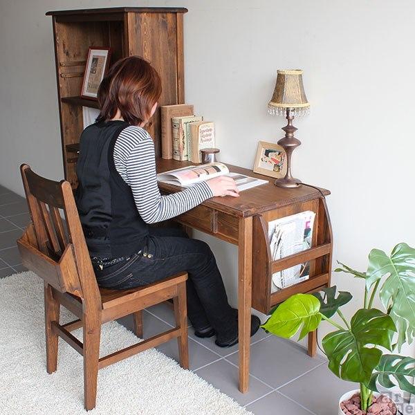 チャーチチェアに座りデスクで本を読む女性