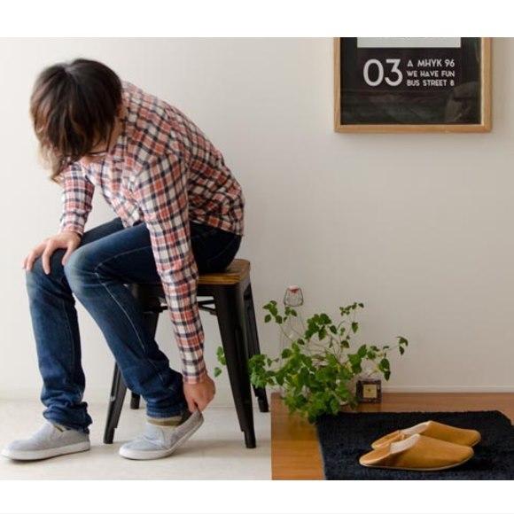 玄関でスツールに座り靴を履く男性 Lewis
