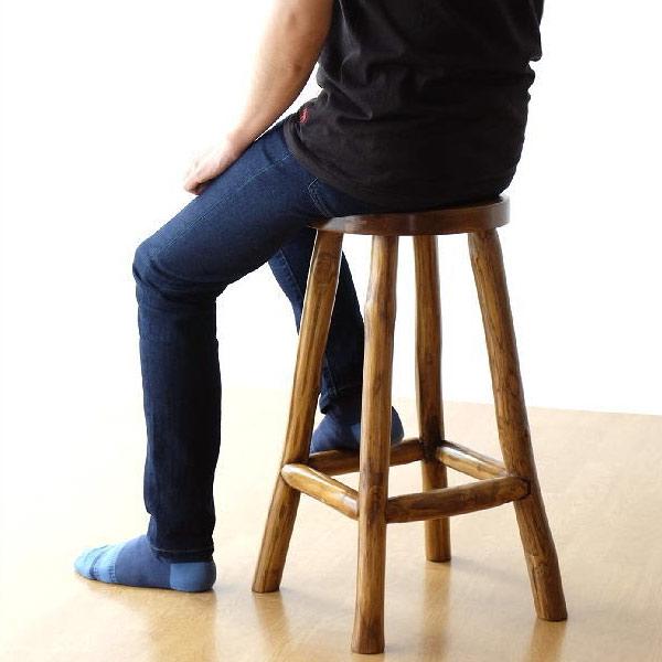 高さ60cmのチーク原木スツールに座る男性