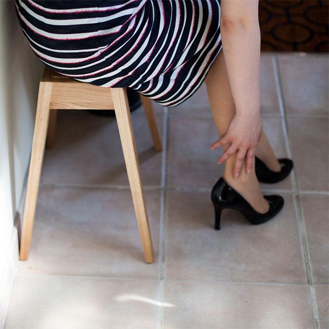 オーク材 b2cスタッキングスツールに座り靴を履く女性
