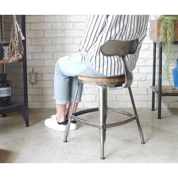 インダストリアル系スチール製チェアに座る女性
