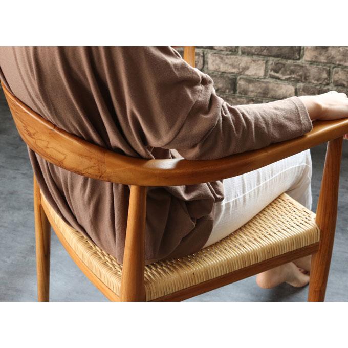 チークと籐のダイニングアームチェアIDENTITY に座る女性