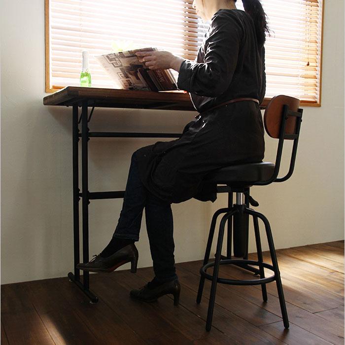 背もたれ付きレトロ調バー・スツールに座る女性