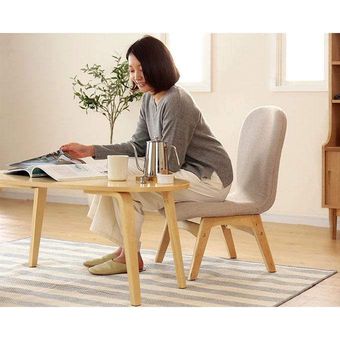 低い椅子に座り本を読む女性