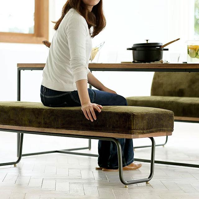 コーデュロイのおしゃれなベンチに座る女性