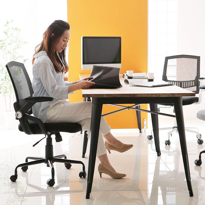 おしゃれなオフィスチェアに座って仕事をする女性