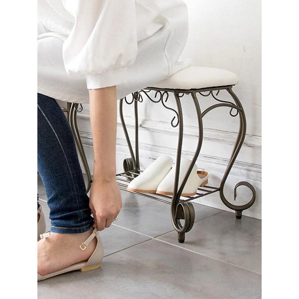 アンティーク調スツールに座り靴を履く女性