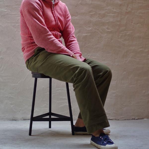 3本脚の無垢材スツールに座る男性