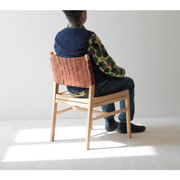 レザーと無垢材の北欧系チェアに座る男性