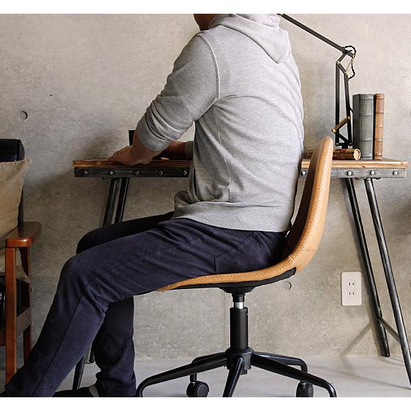 キャメルカラーのヴィンテージ系デスクチェアに座る男性