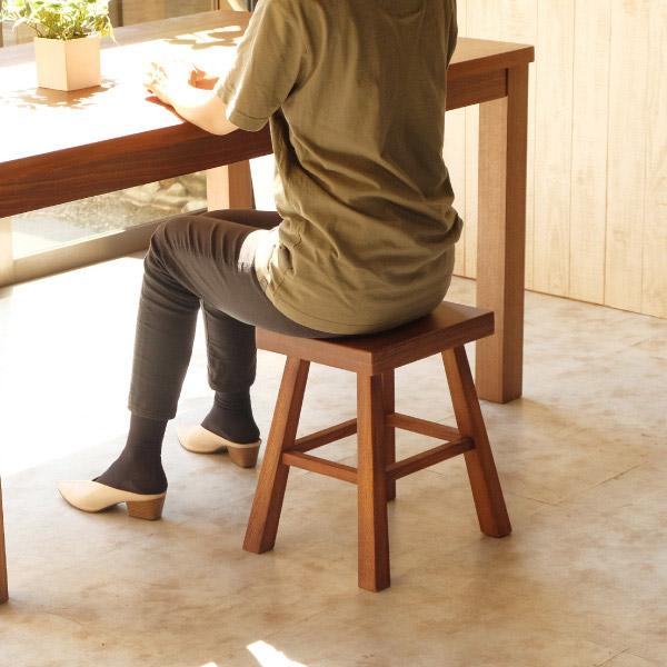 無垢材の四角いスツールに座る女性