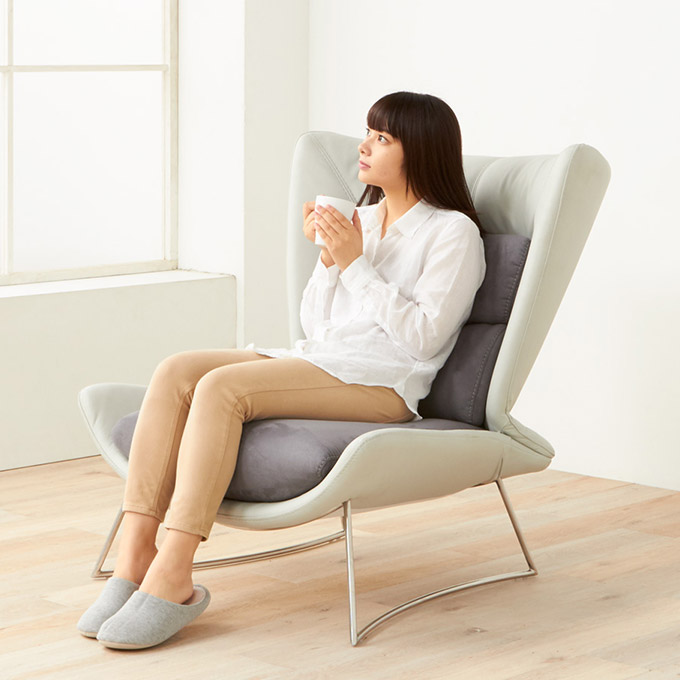 牛革の高級ソファに座る女性