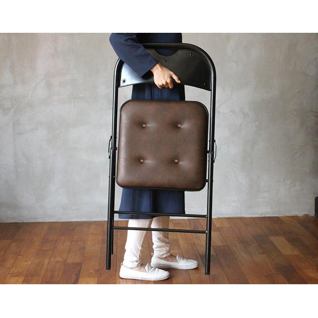 お洒落な折りたたみ椅子を持ち運ぶ女性