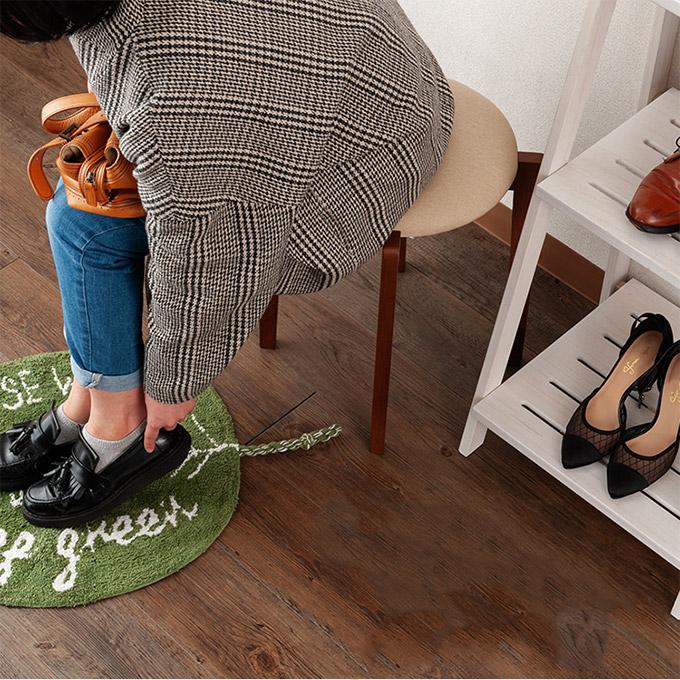 ナチュラル系スツールに座って靴を履く女性